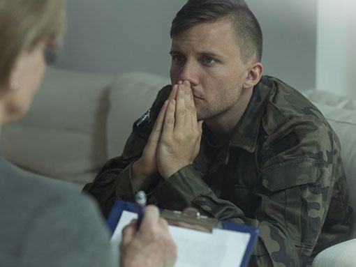 man in military uniform receiving therapy